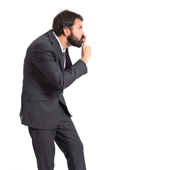 Businessman making silence gesture over isolated white background