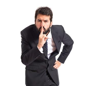孤立した白い背景の上に沈黙のジェスチャーを作るビジネスマン