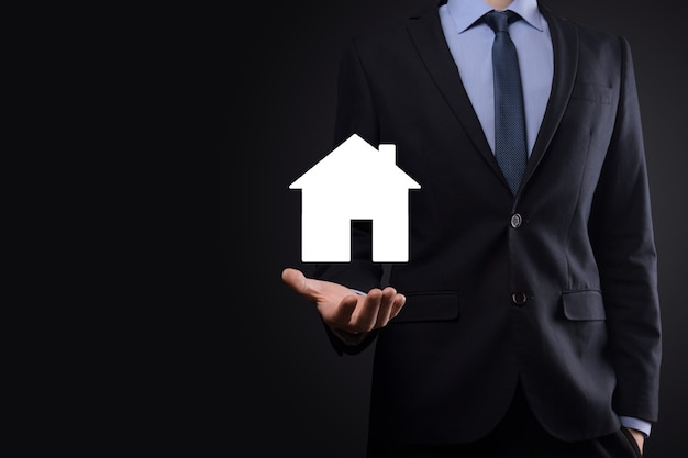 Businessman male hand holding house icon on blue background. property insurance and security concept.real estate concept.banner with copy space.