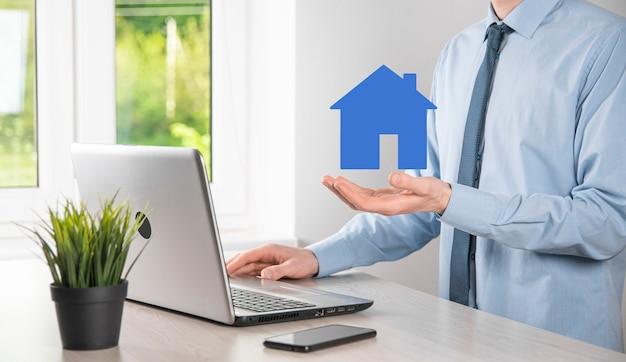 Businessman male hand holding house icon on blue wall. property insurance and security concept.real estate concept.banner with copy space.