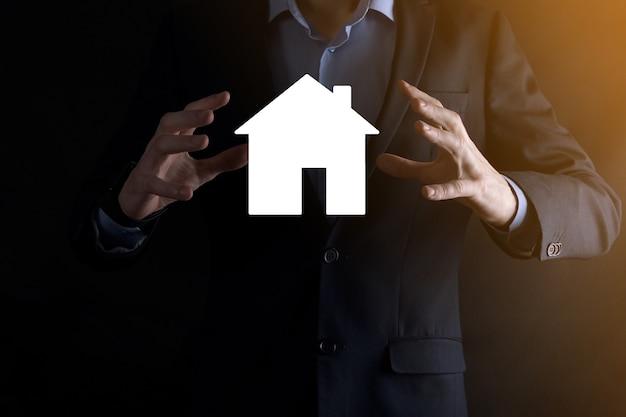 青の背景に家のアイコンを持っているビジネスマンの男性の手。財産保険とセキュリティの概念。不動産の概念。コピースペース付きのバナー。