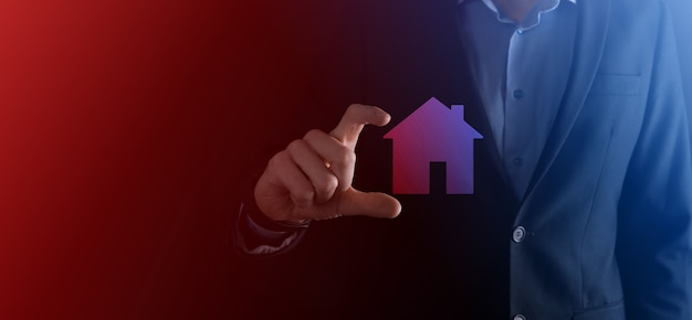 파란색 배경에 집 아이콘을 들고 사업가 남성 손. 재산 보험 및 보안 개념입니다. 부동산 개념입니다. 복사 공간이 있는 배너입니다.