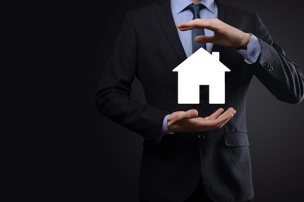 青の背景に家のアイコンを保持しているビジネスマンの男性の手。財産保険とセキュリティの概念。不動産の概念。コピースペース付きのバナー。