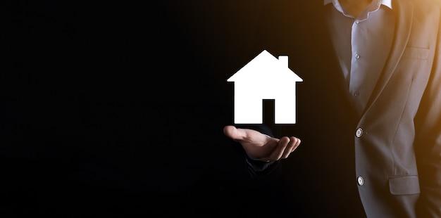 Бизнесмен мужской рукой, держащей значок дома на синем фоне. страхование имущества и концепция безопасности. концепция недвижимости. баннер с копией пространства.