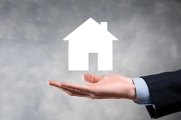 青の背景に家のアイコンを持っているビジネスマンの男性の手。財産保険とセキュリティのコンセプト。不動産のコンセプト。コピー スペース付きのバナー。