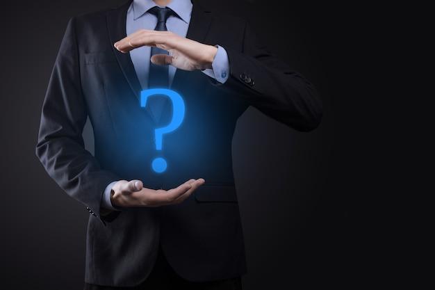 Бизнесмен человек рука держать интерфейс вопросительные знаки подписать сеть. задавайте вопросы в интернете, понятие faq, что, где, когда, как и почему, ищите информацию в интернете.