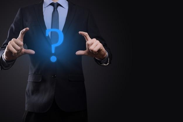 Бизнесмен человек рука держать интерфейс вопросительные знаки подписать сеть. задавайте вопросы онлайн, понятие faq, что где, когда как и почему, ищите информацию в интернете.
