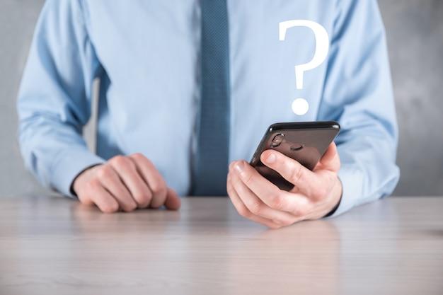 Бизнесмен человек рука держать интерфейс вопросительные знаки подписать сеть. спросите quiestion онлайн, понятие faq, что где, когда, как и почему, ищите информацию в интернете.