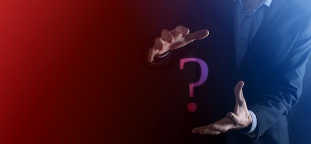 Бизнесмен человек рука держать интерфейс вопросительные знаки подписать сеть. спросите quiestion онлайн, понятие faq, что где, когда, как и почему, ищите информацию в интернете