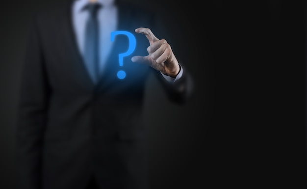 Businessman man hand hold interface question marks sign web. ask quiestion online, faq concept, what where when how and why, search information on internet