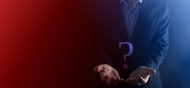Businessman man hand hold interface question marks sign web. ask quiestion online, faq concept, what where when how and why, search information on internet.