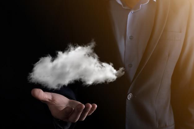 ビジネスマンの手がクラウドを持っています。クラウドコンピューティングの概念、彼の手の上に雲を持つ若いビジネスマンのクローズアップ