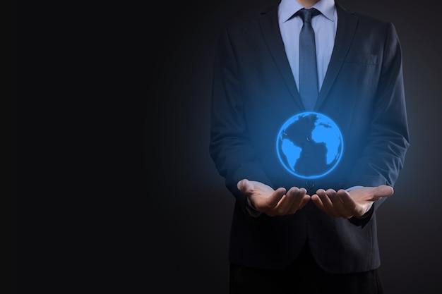 地球のアイコン、デジタルグローブを持っているビジネスマンの男の手。