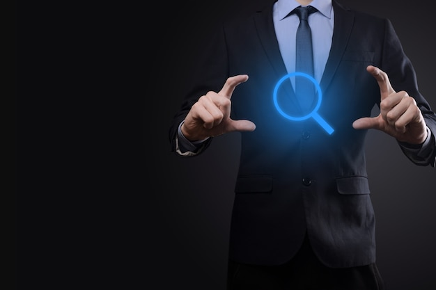 Businessman, man hold in hand magnifying glass icon.business, technology and internet concept