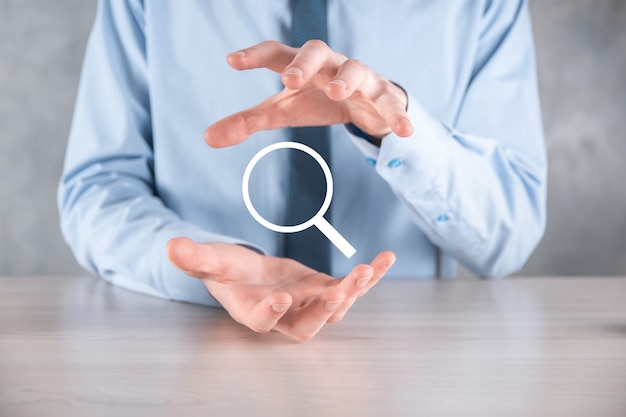 Businessman, man hold in hand magnifying glass icon