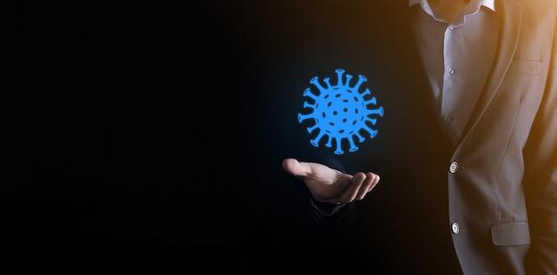 ビジネスマンの男性は、covid呼吸器症候群コロナウイルスと新規コロナウイルスncovの抽象的なウイルス株モデルを手にしています