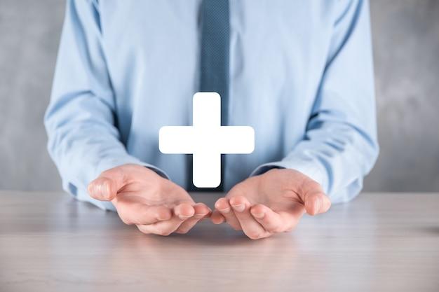 Бизнесмен, мужчина держит в руке, предлагают положительные вещи, такие как прибыль, преимущества, развитие, ксо, представленные знаком плюс. рука показывает знак плюса.