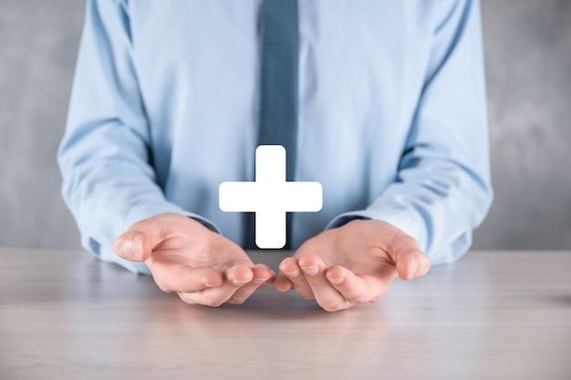 사업가, 남자 손을 잡고 더하기 기호로 표시되는 이익, 혜택, 개발, csr과 같은 긍정적 인 것을 제공합니다.