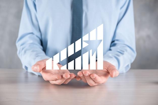 Бизнесмен мужчина держит график с положительным ростом прибыли. план роста графика и увеличение положительных показателей графика в своем бизнесе. более прибыльный и растущий