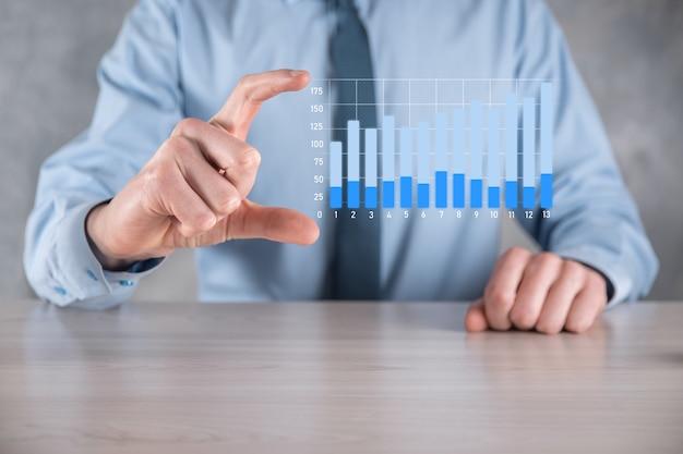 긍정적 인 이익 성장 그래프를 들고 사업가 남자. 그의 사업에서 그래프 성장과 차트 긍정적 지표의 증가를 계획하십시오.
