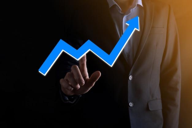 正の利益成長とグラフを保持しているビジネスマン。彼のビジネスにおけるグラフの成長とチャートのポジティブな指標の増加を計画します。より収益性が高く、成長しています。
