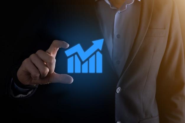 利益の伸びがプラスのグラフを持つビジネスマンの男性。彼のビジネスにおけるグラフの成長とチャートのポジティブ インジケーターの増加を計画します。より収益性が高く、成長しています。