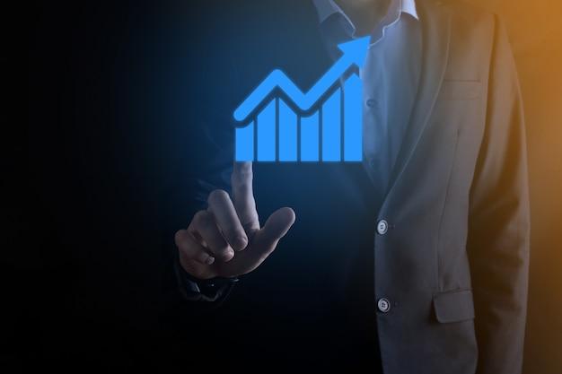 Бизнесмен мужчина держит график с положительным ростом прибыли. план роста графика и увеличение положительных показателей графика в своем бизнесе. более прибыльный и растущий.