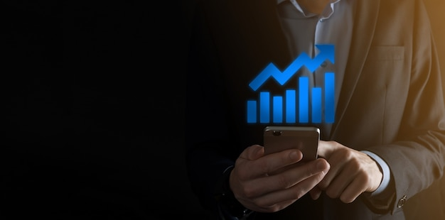긍정적인 이익 성장 그래프를 들고 사업가 남자. 그의 비즈니스에서 그래프 성장 및 차트 긍정적 지표의 증가를 계획합니다. 더 수익성 있고 성장합니다.