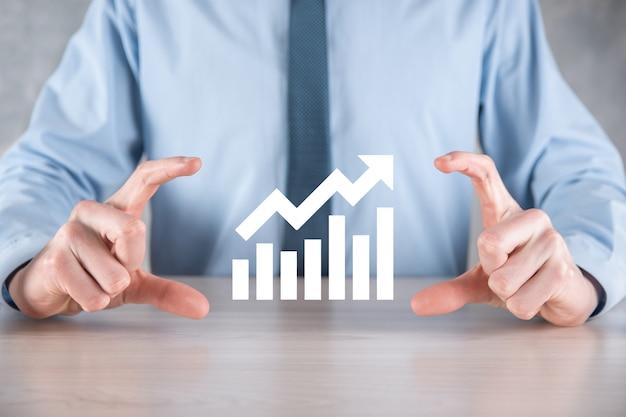 Бизнесмен мужчина держит график с положительным ростом прибыли. рост графика плана и увеличение положительных показателей графика