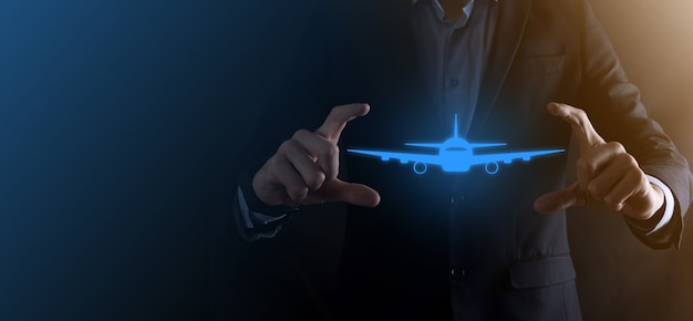 Бизнесмен мужчина держит в руках значок самолета