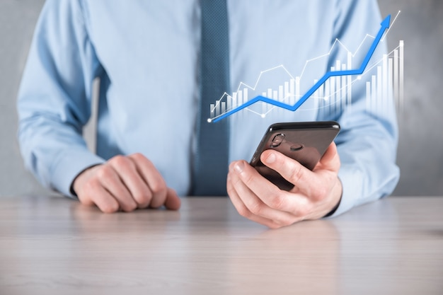 Businessman man holding a graph with positive profits growth. plan graph growth and increase of chart positive indicators in his business.more profitable and growing