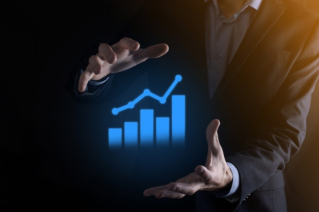Businessman man holding a graph with positive profits growth. plan graph growth and increase of chart positive indicators in his business.more profitable and growing.