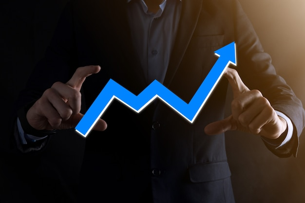 Businessman man holding a graph with positive profits growth