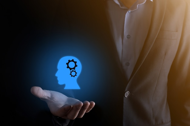 Businessman man holding a man icon with gears in his head. artificial intelligence.