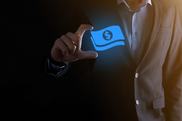 Businessman man holding money coin icon in his hands.growing money concept for business investment and finance. usd or us dollar on dark tone background.