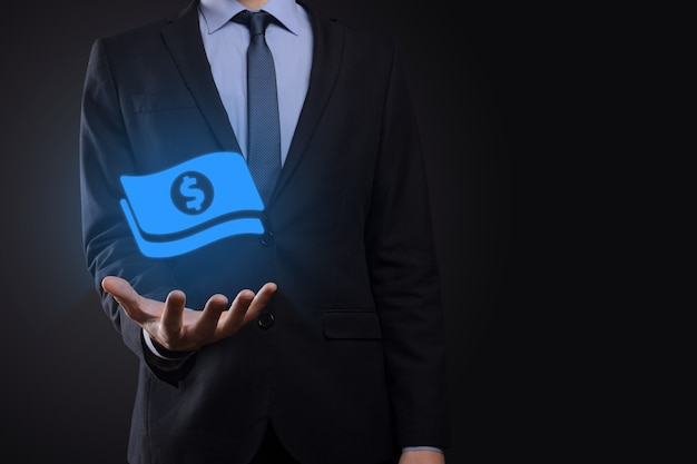 Businessman man holding money coin icon in his hands.growing money concept for business investment and finance. usd or us dollar on dark tone background