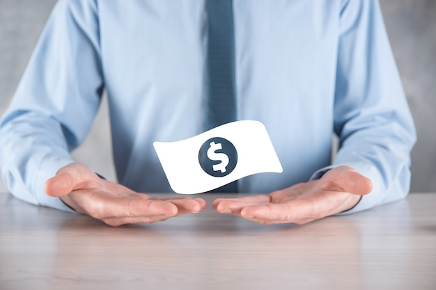 Businessman man holding money coin icon in his hands.growing money concept for business investment and finance. usd or us dollar on dark tone wall.