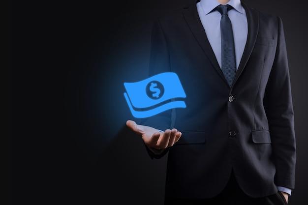彼の手でお金のコインアイコンを保持しているビジネスマン。事業投資と金融のためのお金の概念を成長させます。暗いトーンの背景に米ドルまたは米ドル