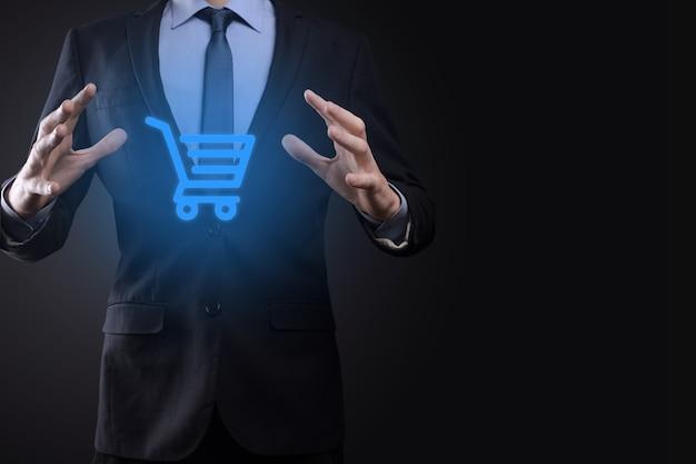 Бизнесмен мужчина держит тележку тележки мини-тележку в интерфейсе цифровой оплаты бизнеса. бизнес, коммерция и концепция покупок.