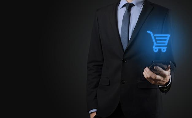 비즈니스 디지털 결제 인터페이스에서 쇼핑 카트 트롤리 미니 카트를 들고 사업가 남자. 비즈니스, 상업 및 쇼핑 개념입니다.