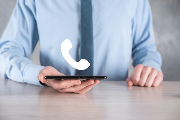 灰色の背景にネクタイとシャツを着たビジネスマンの男性は、電話のアイコンを保持します。