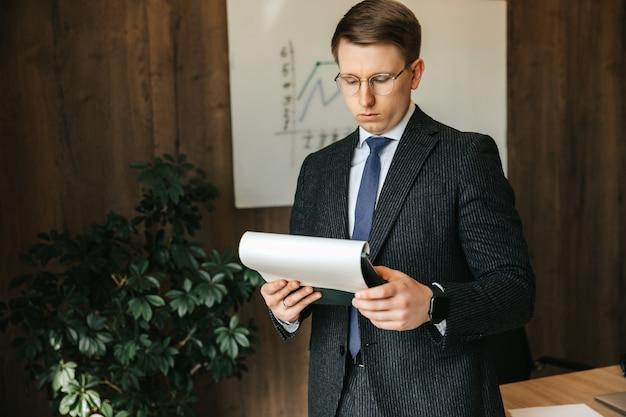 眼鏡をかけたビジネスマンの男性は、オフィスで文書を調べます。