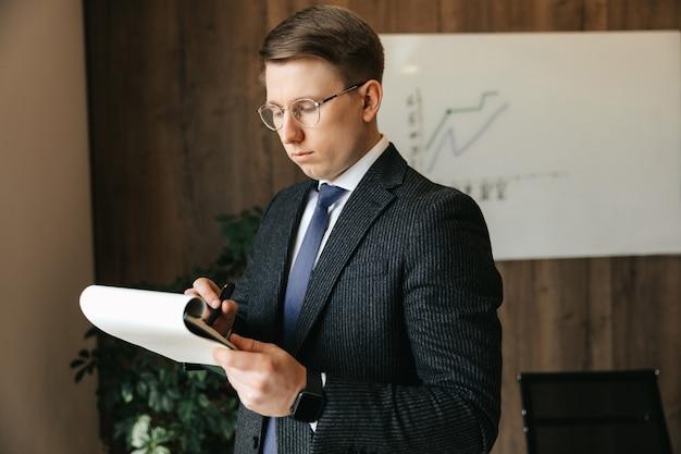 안경, 사업가 남자 사무실에서 서류를 씁니다.