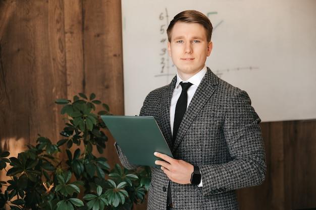 彼のオフィスのビジネスマンの男性は、彼の手に書類とペンで立っていますサラリーマン古典的なスーツの男性