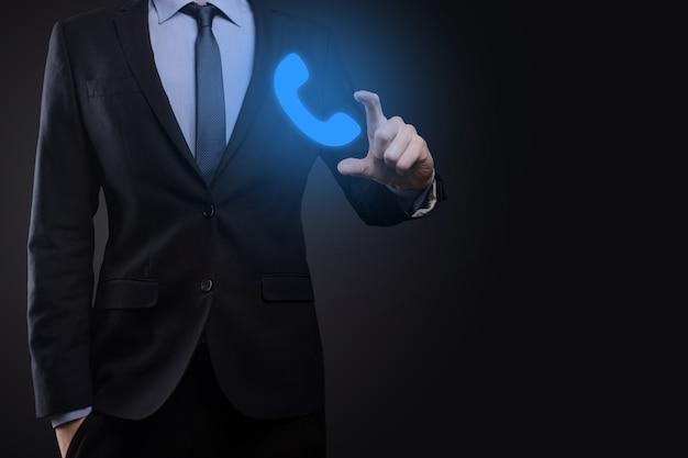 Бизнесмен человек в костюме на черном фоне удерживайте значок телефона. позвоните сейчас центр поддержки делового общения концепция технологии обслуживания клиентов.