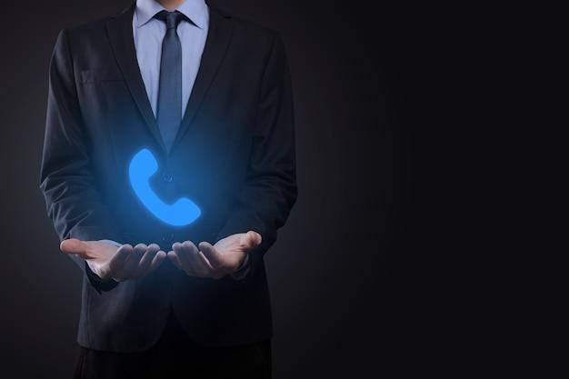 黒の背景にスーツを着たビジネスマンが電話アイコンを保持します。今すぐお電話