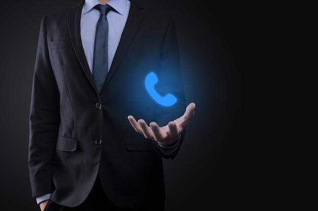 黒の背景にスーツのビジネスマン男は電話アイコンを保持します。