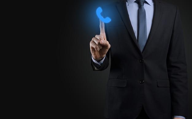 黒の背景にスーツを着たビジネスマンは、電話のアイコンを保持します。