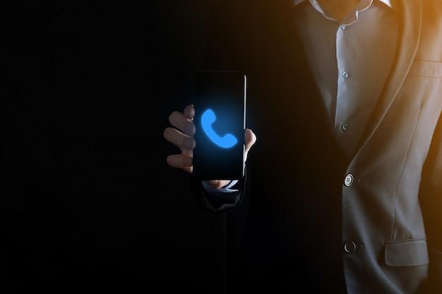 Бизнесмен человек в костюме на черной поверхности держит значок телефона