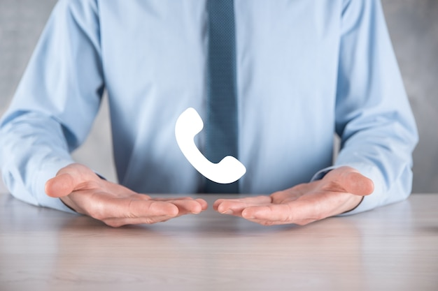 Businessman man in a shirt with a tie on gray wall hold phone icon.call now business communication support center customer service technology concept.